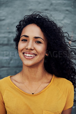 Buy stock photo Cropped portrait of an attractive young woman standing outside alone against a gray background and smiling
