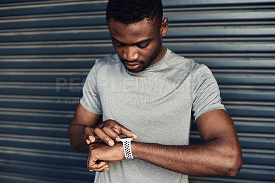 Buy stock photo Shot of a sporty young man checking his watch while exercising against a grey background