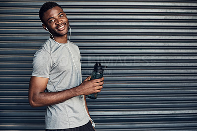 Buy stock photo Portrait of a sporty young man drinking water while exercising against a grey background