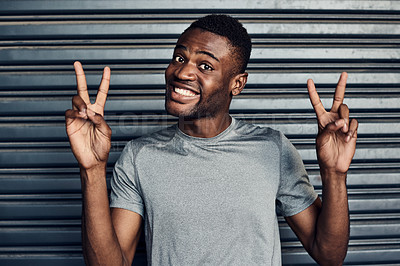 Buy stock photo Portrait of a sporty young man making the peace sign against a grey background