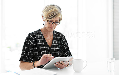 Buy stock photo Cropped shot of an attractive mature businesswoman looking serious while working with a digital tablet in her office