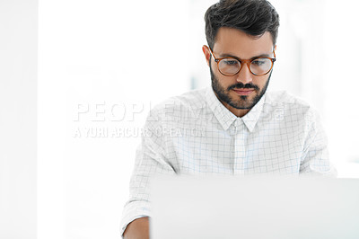 Buy stock photo Cropped shot of a handsome young businessman looking serious while working on a laptop in his office