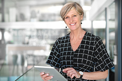 Buy stock photo Cropped portrait of an attractive mature businesswoman using a digital tablet while standing in a modern office