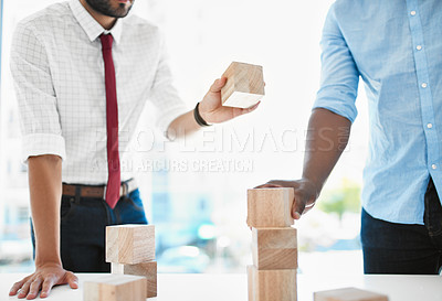 Buy stock photo Cropped shot of two unrecognizable businessmen having a discussion using building blocks in a modern office