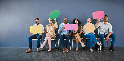 Buy stock photo Studio shot of a diverse group of businesspeople holding speech bubbles while sitting against a grey background