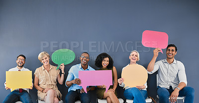 Buy stock photo Studio portrait of a diverse group of businesspeople holding speech bubbles while sitting against a grey background