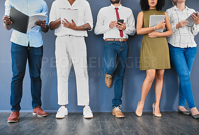 Buy stock photo Studio shot of a diverse group of unrecognizable businesspeople keeping occupied while waiting in line against a grey background