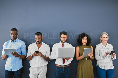 Buy stock photo Studio shot of a diverse group of businesspeople using wireless technology while waiting in line against a grey background