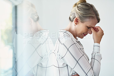 Buy stock photo Cropped shot of an attractive mature businesswoman suffering with a headache while standing in a modern office