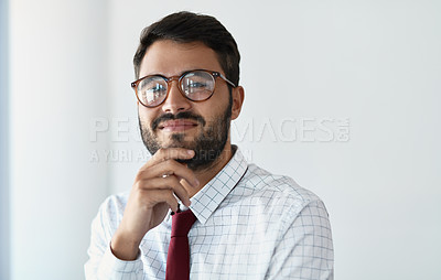 Buy stock photo Cropped portrait of a handsome young businessman looking thoughtful while standing in a modern office