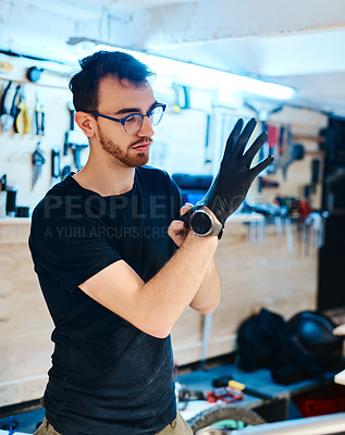 Buy stock photo Shot of a young man putting on protective gloves while working in a bicycle repair shop
