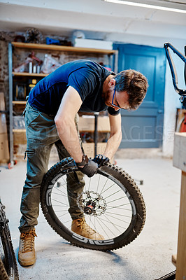 Buy stock photo Shot of a male handyman fixing bicycles in his workshop