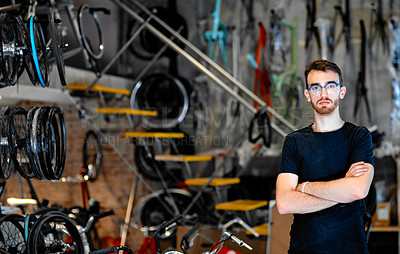 Buy stock photo Portrait of a young man standing in a bicycle workshop