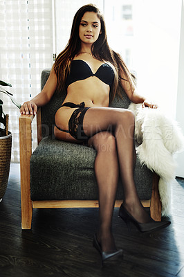 Buy stock photo Full length portrait of an attractive young woman sitting in a chair in her bedroom while wearing lingerie