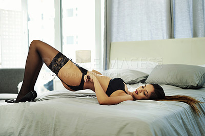 Buy stock photo Full length shot of an attractive young woman posing seductively on her bed while wearing lingerie