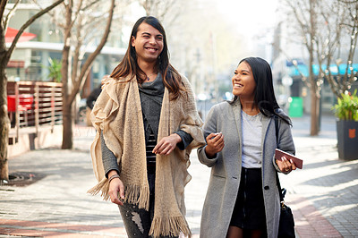 Buy stock photo Cropped shot of two affectionate young friends having a discussion while walking in the city