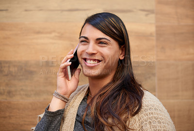 Buy stock photo Cropped shot of a young gender fluid person smiling while taking a phonecall outdoors