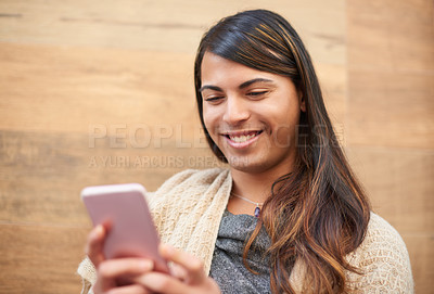 Buy stock photo Cropped shot of a young gender fluid person smiling while using a smartphone outdoors