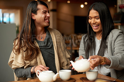Buy stock photo Cropped shot of two affectionate young friends laughing together while serving themselves coffee in a cafe