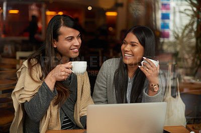 Buy stock photo Cropped shot of two young friends having coffee while using a laptop together in a cafe