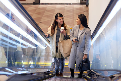 Buy stock photo Full length shot of two affectionate young friends going up an escalator in a shopping mall during the day