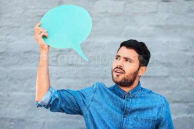 Buy stock photo Cropped shot of a handsome young man looking skeptical while holding a speech bubble against a brick wall