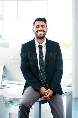 Buy stock photo Cropped portrait of a handsome young businessman smiling while sitting on his desk in a modern office