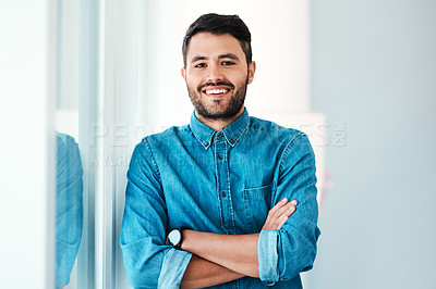 Buy stock photo Cropped portrait of a handsome young businessman smiling while standing with his arms crossed in an office
