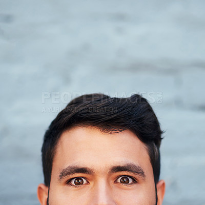 Buy stock photo Cropped portrait of a young man's face peeking from below against a brick wall
