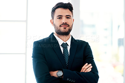 Buy stock photo Cropped portrait of a handsome young businessman standing with his arms crossed in a modern office