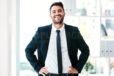 Buy stock photo Cropped portrait of a handsome young businessman smiling while standing with his arms on his waist in a modern office