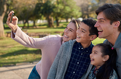 Buy stock photo Shot of a happy young family taking a selfie together in the park
