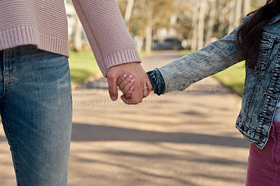 Buy stock photo Cropped shot of a little girl holding her mother's hand while going for a walk in the park