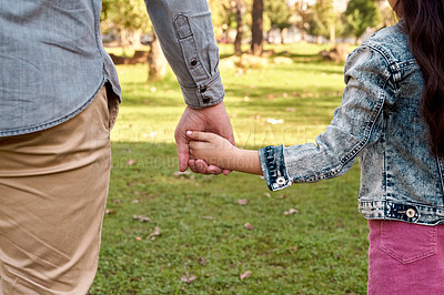 Buy stock photo Cropped shot of a little girl holding her father's hand while going for a walk in the park