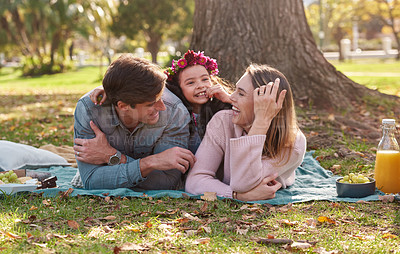 Buy stock photo Shot of a happy young family enjoying a picnic in the park
