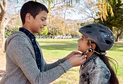 Buy stock photo Shot of a young boy helping to secure his sister's helmet before she rides her bicycle in the park