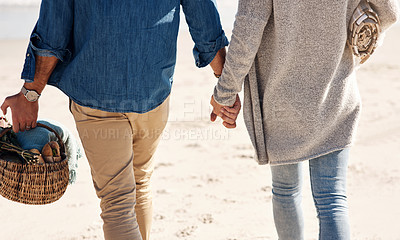 Buy stock photo Cropped shot of an unrecognizable couple walking hand in hand on the beach