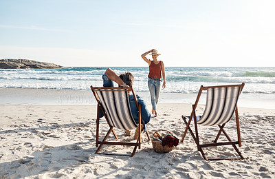 Buy stock photo Rearview shot of a middle aged couple sitting in their beach chairs on the the beach