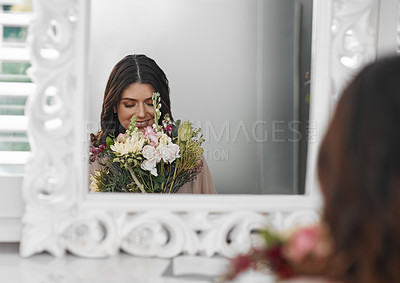Buy stock photo Cropped shot of a beautiful woman smelling flowers while sitting in front of the mirror
