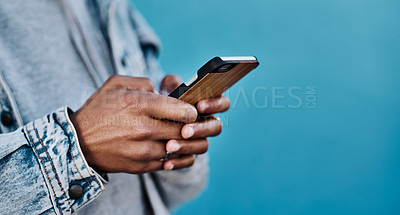 Buy stock photo Cropped shot of an unrecognizable man using his cellphone against a blue background