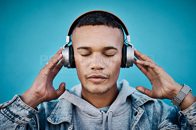 Buy stock photo Shot of a handsome young man wearing headphones while posing against a blue background