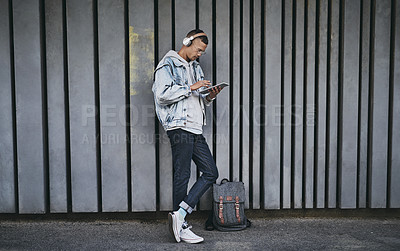 Buy stock photo Shot of a man using a digital tablet and wearing headphones while standing outside