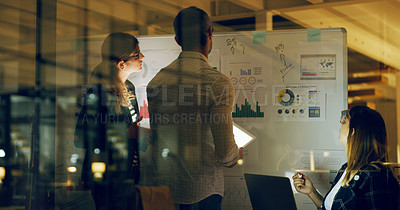 Buy stock photo Cropped shot of a group of business colleagues using a whiteboard and technology to brainstorm in the office at night