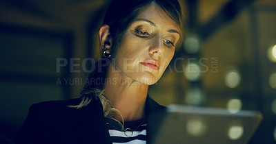 Buy stock photo Cropped shot of an attractive young businesswoman standing alone and using a tablet in the office late at night