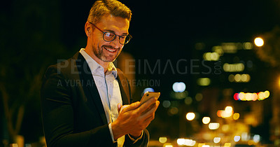 Buy stock photo Cropped shot of a handsome young businessman standing outside alone and texting on his cellphone late at night