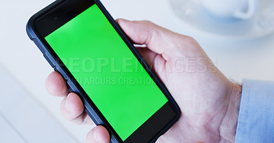 Buy stock photo Cropped shot of an unrecognizable businessman sitting alone and showing a green screen on his cellphone in the office
