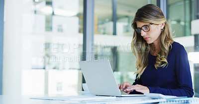 Buy stock photo Cropped shot of an unrecognizable young businesswoman sitting alone and typing on her laptop in the office