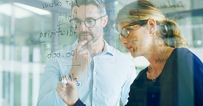 Buy stock photo Cropped shot of two business colleagues standing and writing on a clear board during a brainstorm session in the office
