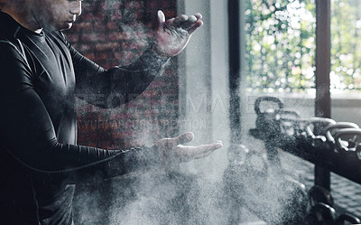 Buy stock photo Cropped shot of an unrecognizable man dusting his hands with chalk powder at the gym