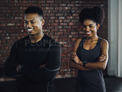 Buy stock photo Shot of a confident young man and woman working out at a gym
